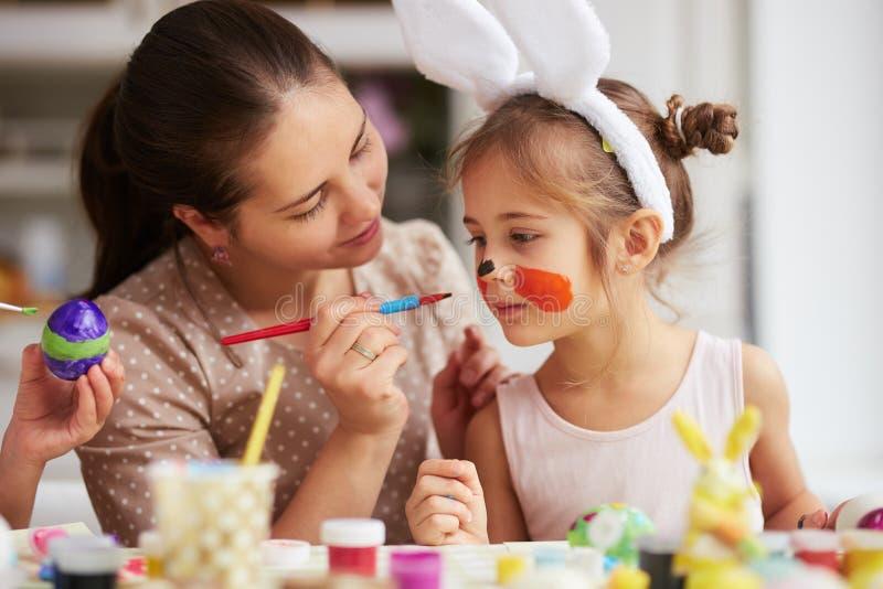 Mutter zeichnet auf das Gesicht der Tochter beim Färben der Eier für die Ostern-Tabelle in der gemütlichen hellen Küche lizenzfreie stockbilder