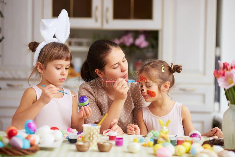 Mutter zeichnet auf das Gesicht der Tochter, während sie und ihre zwei kleinen Töchter mit den weißen Ohren des Kaninchens auf ih stockfoto