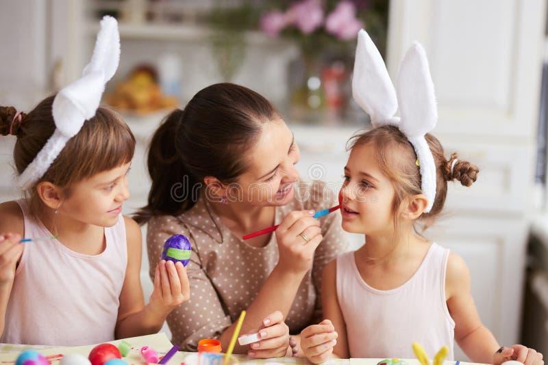 Mutter zeichnet auf die Backe der Tochter, während sie und ihre zwei kleinen Töchter mit den weißen Ohren des Kaninchens auf ihre lizenzfreie stockfotos