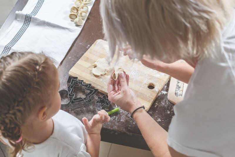 Mutter zeigt kleiner Tochter, wie man Mehlklöße macht lizenzfreie stockfotografie
