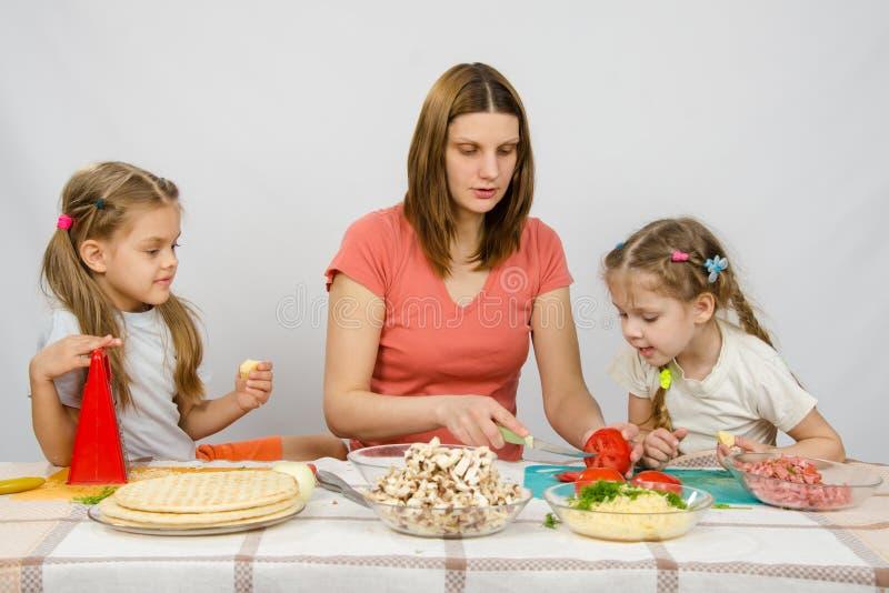 Mutter zeigt zwei junge Töchter am Küchentisch als die Schnitttomatenpizza stockfotos