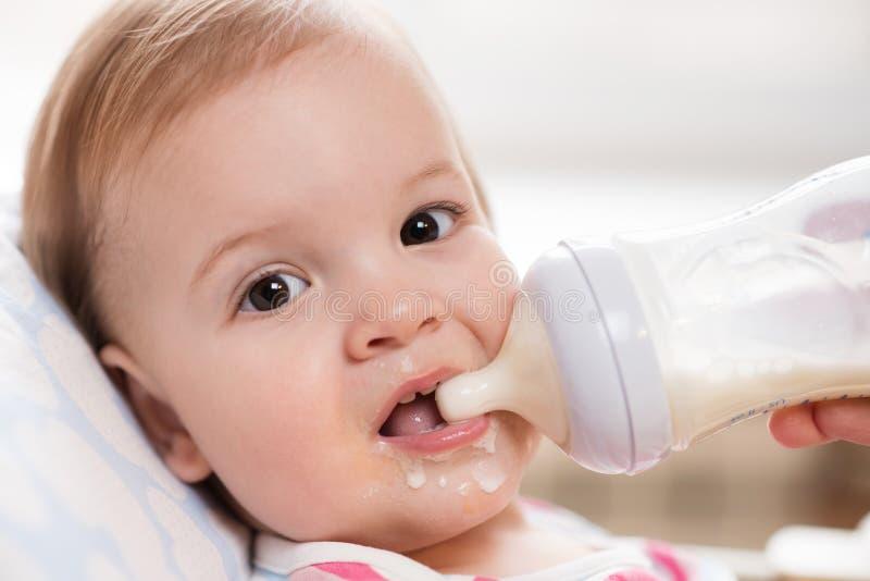 Mutter zieht Baby von einer Flasche Milch ein stockfoto