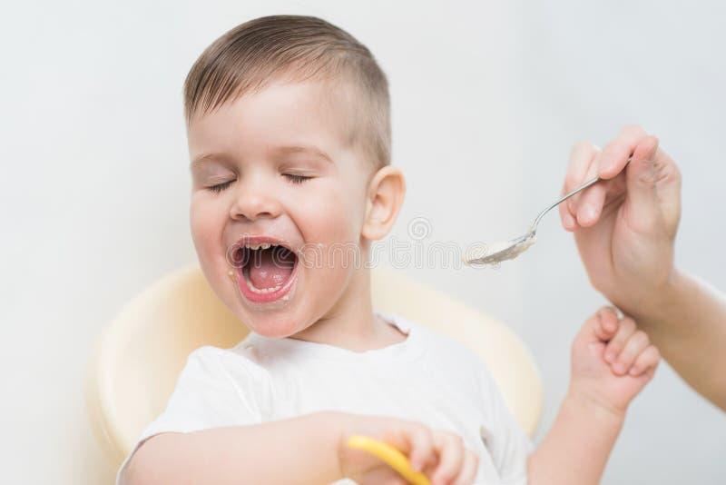 Mutter zieht das Baby ein und er dreht sich weg und möchte nicht essen lizenzfreies stockbild
