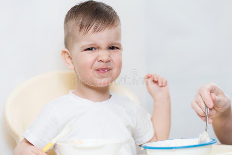 Mutter zieht das Baby ein und er dreht sich weg und möchte nicht essen stockbild