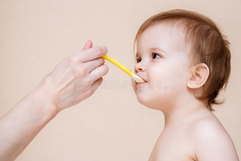 Mutter zieht das Baby mit Fruchtmus ein stockfoto