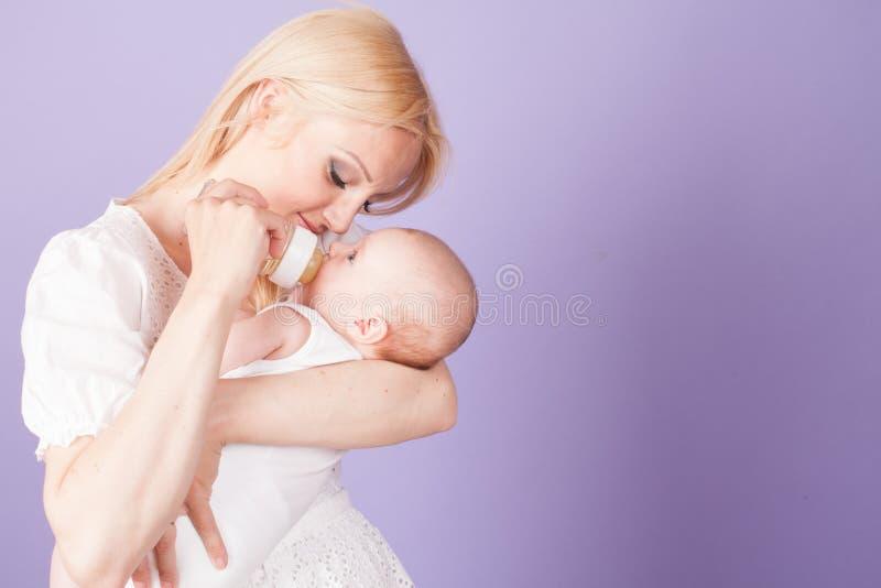 Mutter zieht das Baby von der Flasche mit der Brustwarze ein lizenzfreie stockbilder