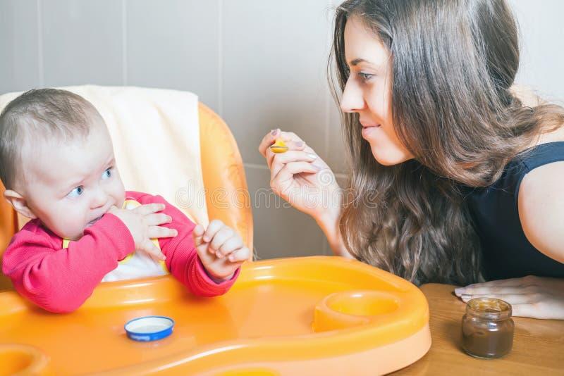 Mutter zieht das Babypüree ein Gesunde und natürliche Säuglingsnahrung stockbild