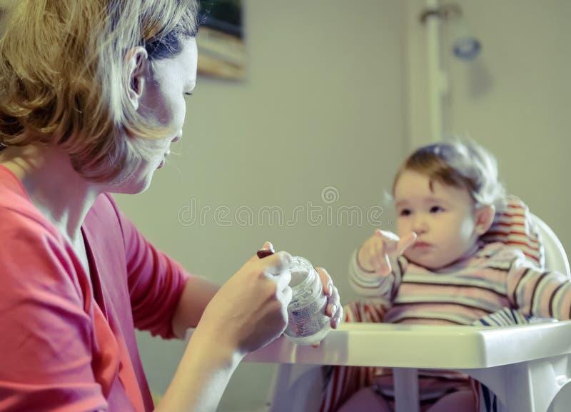 Mutter zieht ihr Baby mit einem Löffel ein stockfotografie