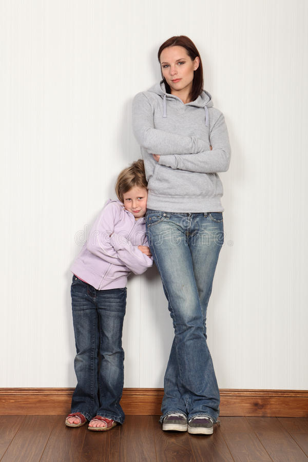 Mutter zu Hause mit ihrer schüchternen jungen Tochter lizenzfreie stockfotografie
