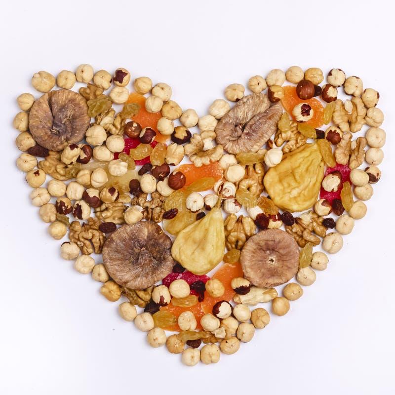 Mutterblandning och torkade frukter i hjärta Shape på den vita fyrkanten för bästa sikt för bakgrund arkivfoton