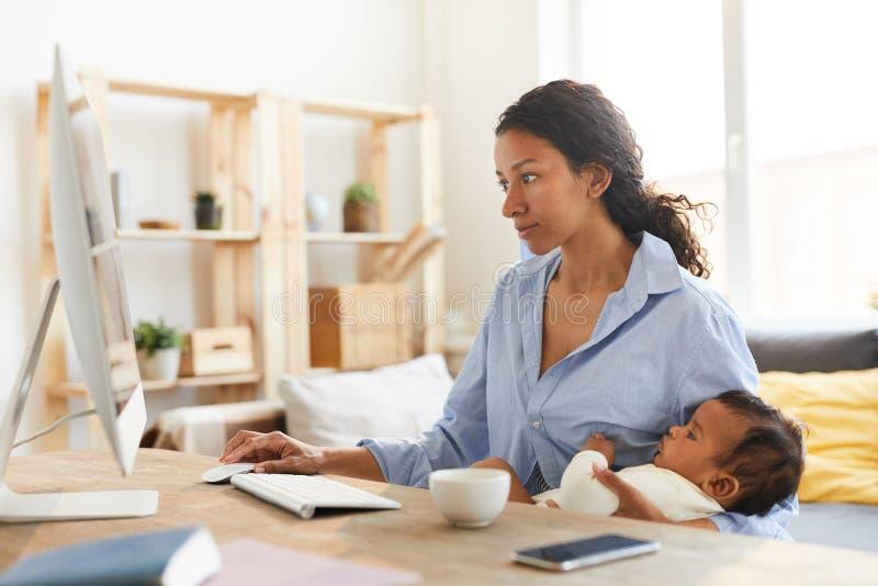 Mutterdesigner, der an Projekt bei der Pflege des Babys arbeitet stockbilder