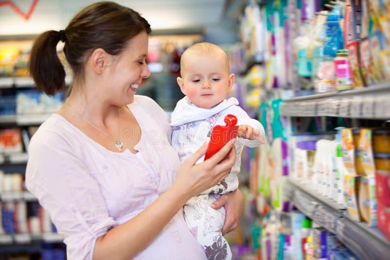 Muttereinkaufen mit Schätzchen im Supermarkt stockbilder
