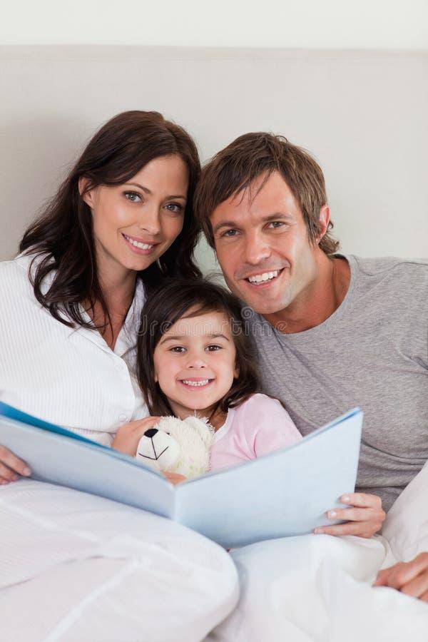 Muttergesellschaft, die eine Geschichte zu ihrer Tochter lesen stockbilder