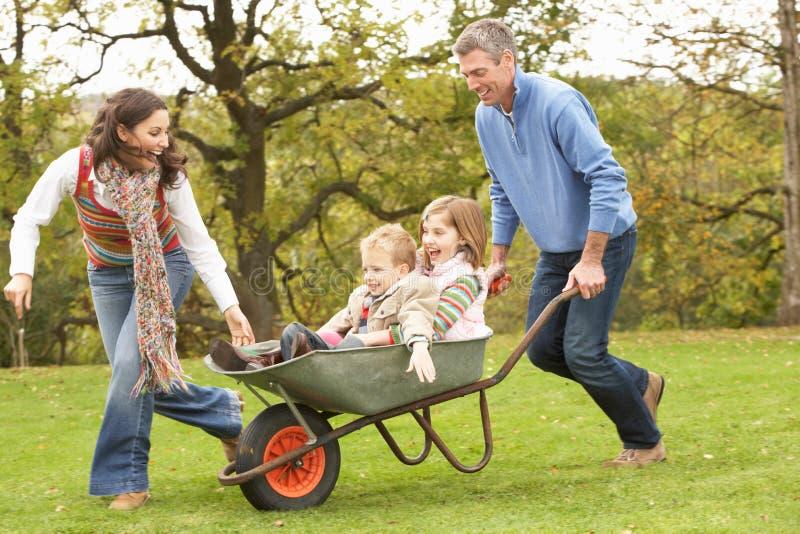 Muttergesellschaft, die Kindern Fahrt in der Schubkarre geben stockbild