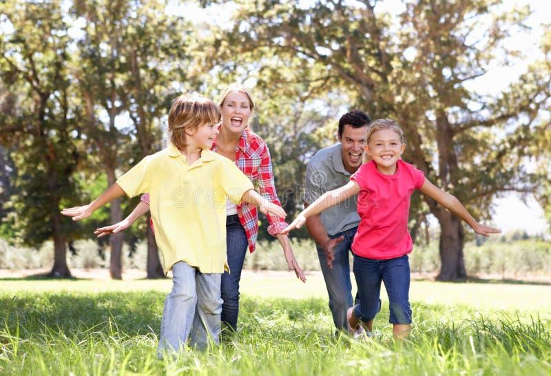 Muttergesellschaft, die mit Kindern im Land spielen lizenzfreie stockbilder