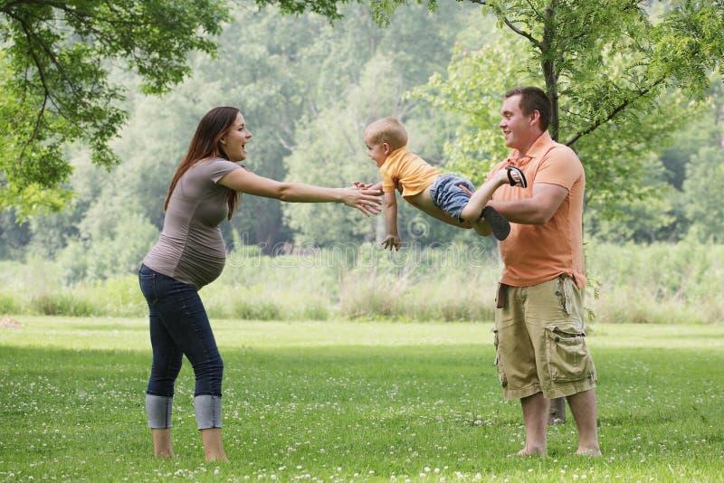 Muttergesellschaft, die mit Sohn draußen spielen. lizenzfreie stockfotos