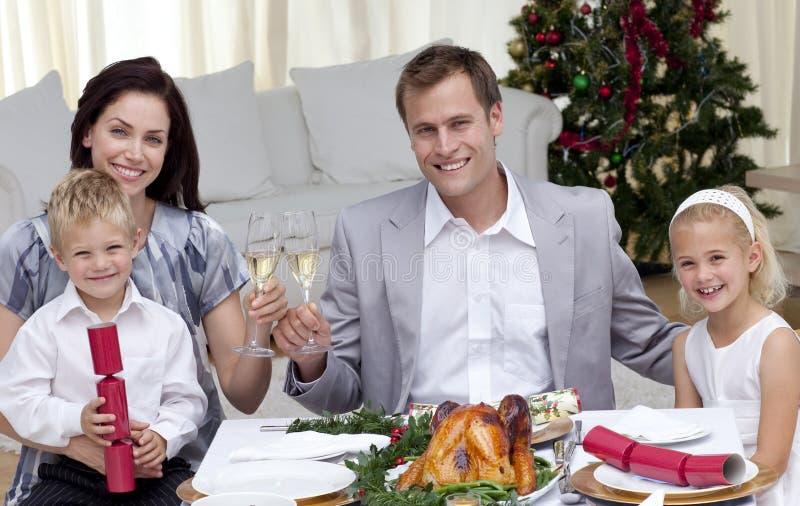 Muttergesellschaft, die mit Wein im Weihnachtsabendessen rösten stockfoto