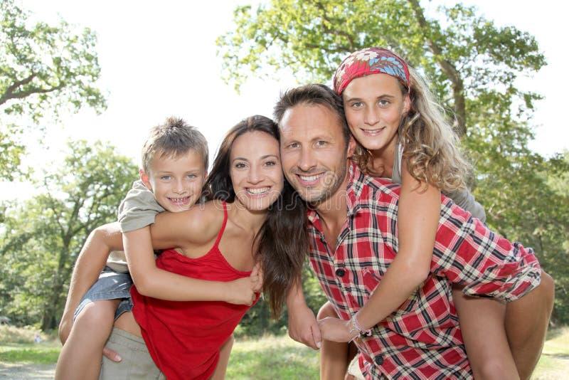 Muttergesellschaft, die piggyback den Kindern Fahrt geben lizenzfreie stockfotos