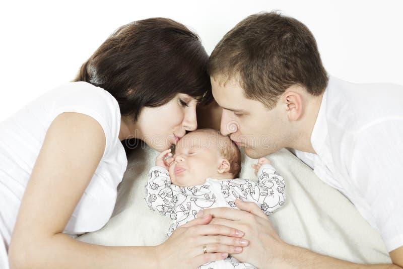 Muttergesellschaft, die schlafendes neugeborenes Schätzchen küssen stockfotografie