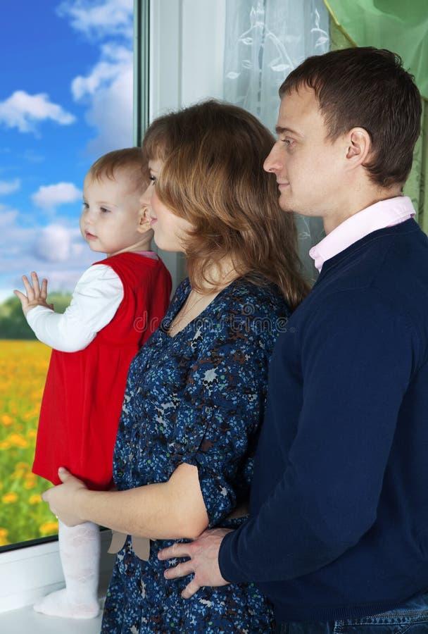 Muttergesellschaft Mit Dem Kind, Welches Heraus Das Fenster Schaut Stockbild