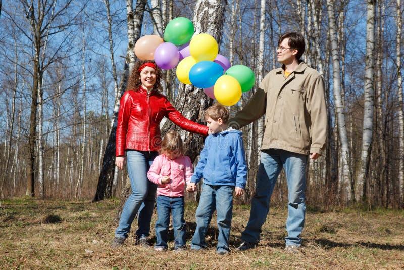 Muttergesellschaft mit Kindern gehen in Park mit Ballonen stockfotografie