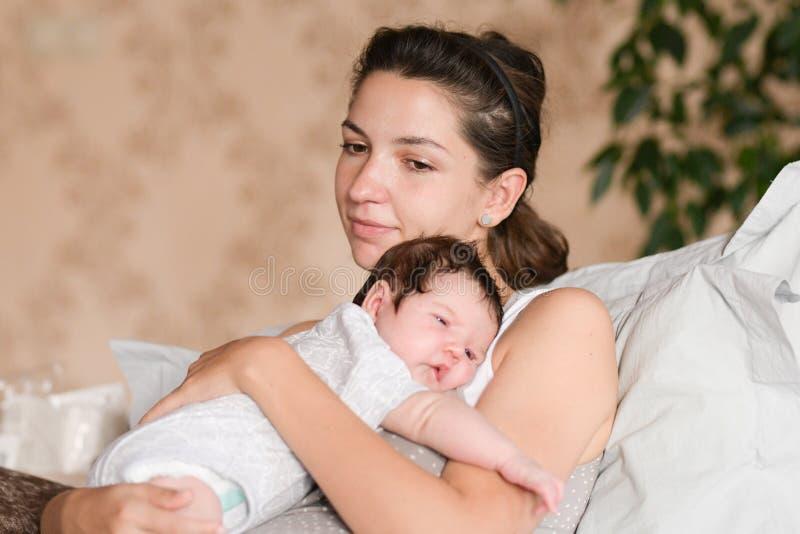 Mutterh?nde Bemuttern Sie das Halten des Kopfes ihres neugeborenen Sohns in den H?nden Das Baby auf H?nden an der Mama Liebende M stockfotografie