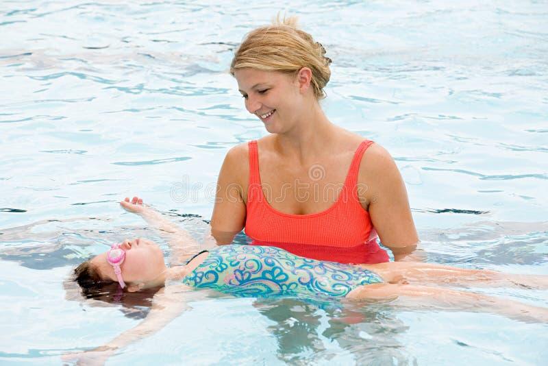 Mutterhelfende Tochter, zum auf sie zurück zu schwimmen lizenzfreies stockbild