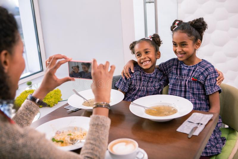 Mutterholding Smartphone, der Foto von ihren netten stilvollen Töchtern macht stockfotos