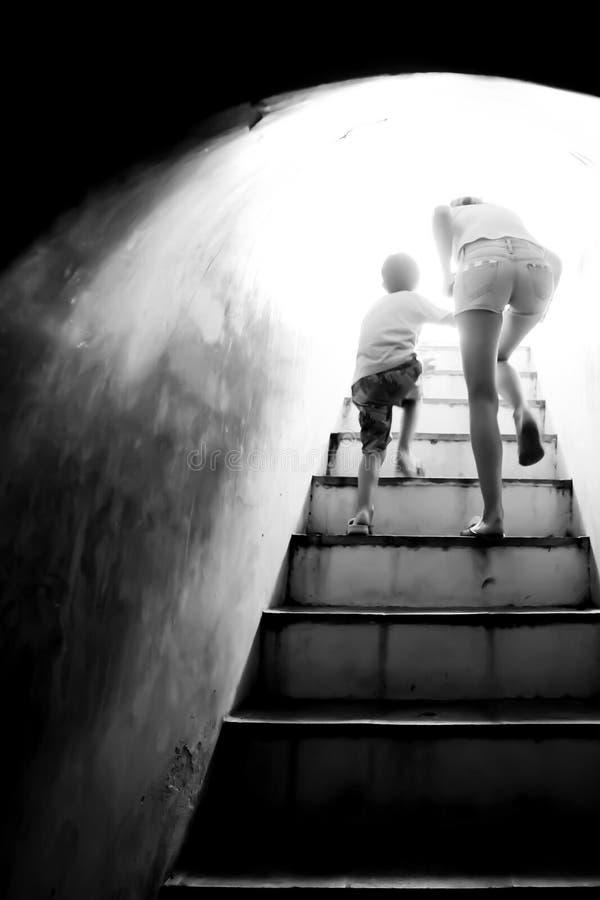 Mutterholdinghand ihr Sohn, der herauf die Treppe zum Licht des hellen Sonnenscheins am Ende des dunklen Tunnels geht stockbild