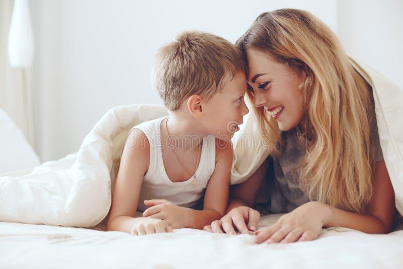 Mutterspiele mit Sohn im Bett lizenzfreie stockfotografie