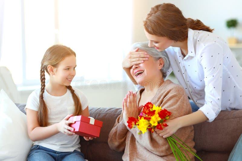 Muttertag! drei Generationen Familienmutter, -großmutter und -tochter beglückwünschen am Feiertag, geben Blumen stockbilder