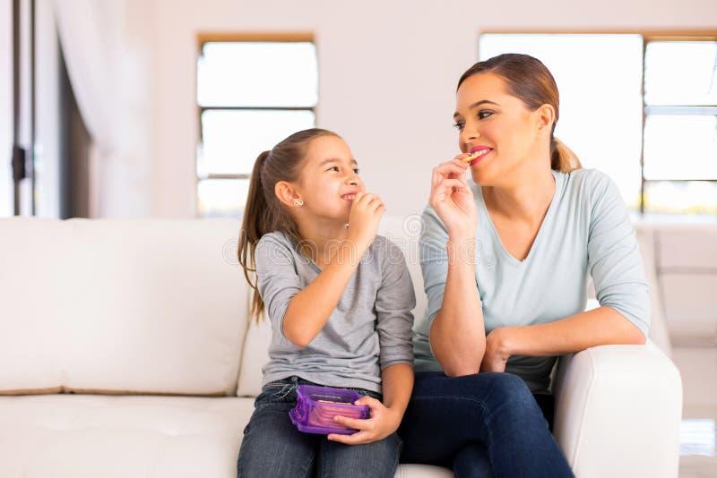 Muttertochter, die Cracker isst stockfotos