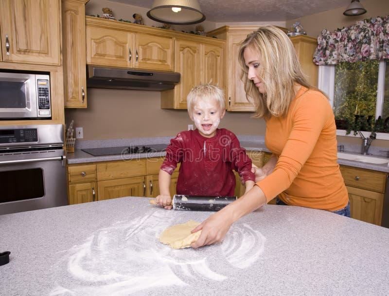 Mutterunterrichtender Sohn, zum des Teigs heraus zu rollen stockfoto