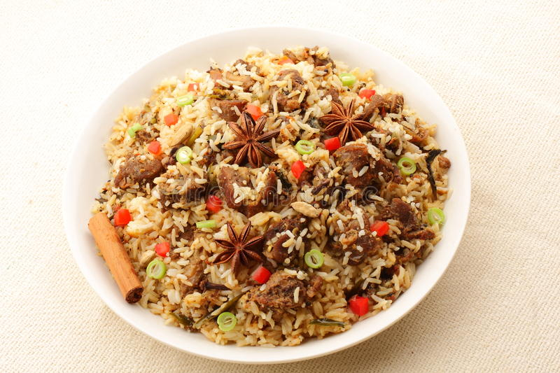 Mutton(lamb) biriyani. Mutton biriyani- It is a medley of rice,mutton(lamb) vegetables.The rice is browned in oil and then mixed with vegetables,spices, nuts stock photography