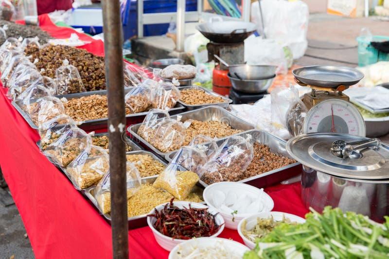 Muttrar och kryddaförsäljning på den asiatiska gatamarknaden arkivbild