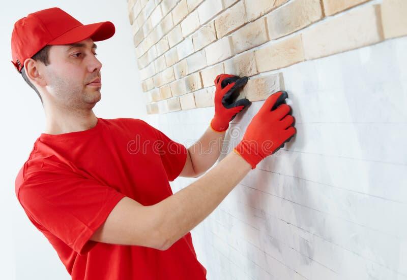 Muur die het werk met baksteen door professionele metselaarsarbeider onder ogen zien stock fotografie