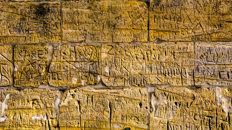 Muur met kalksteenbakstenen met onleesbare gravures die door mensen naarmate de tijd verstrijkt zijn geschreven royalty-vrije stock afbeelding