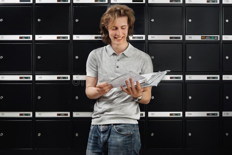 Muur van brievenbussen en een brievenbesteller stock foto