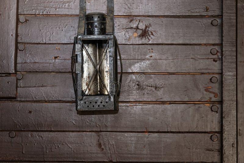 Muur van bruine oude raad met een oude kerosinelantaarn stock foto