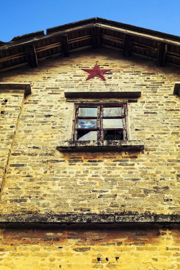Muur van dilapidated huis met een gebroken venster, muur van de verlagingsbouw of slecht huis stock foto's