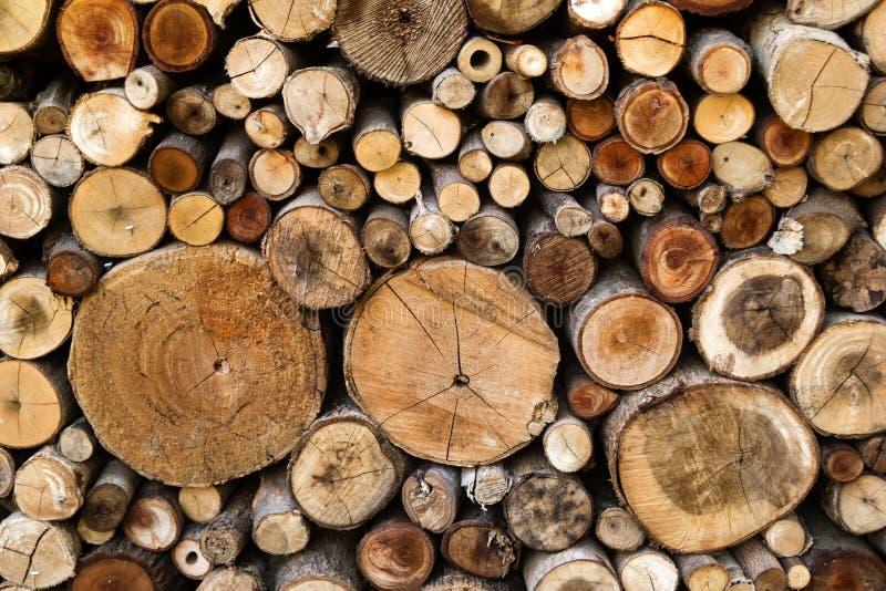 Muur van droge gehakte die brandhoutlogboeken omhoog bovenop elkaar in een stapel worden gestapeld De houten textuur van de close stock foto