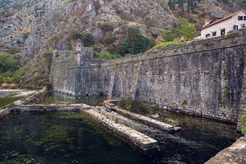 Muur van een oude steenvesting door het water stock fotografie