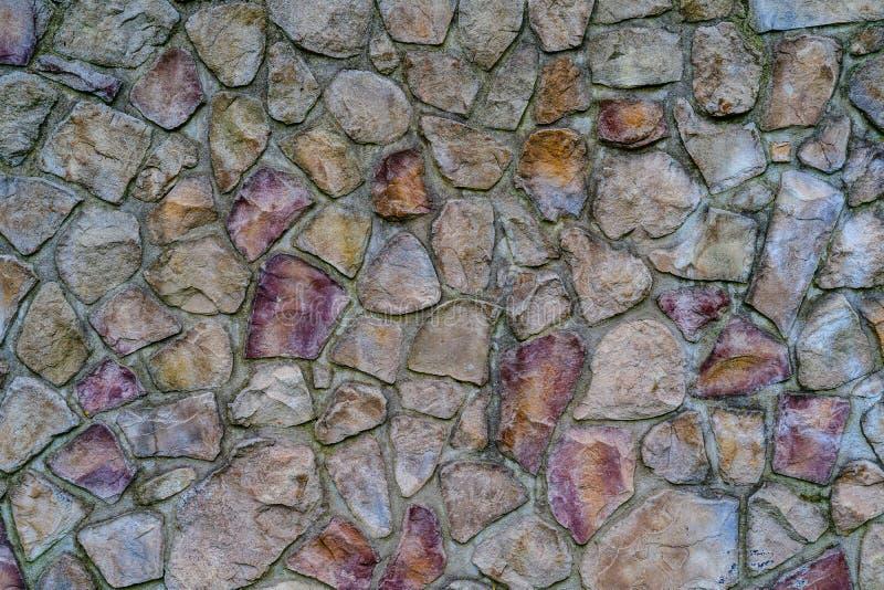Muur van gekleurde die stenen met cement, achtergrond worden vastgemaakt stock afbeeldingen