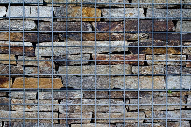 Muur van rivierstenen aanhoudend door metaal netto royalty-vrije stock afbeelding