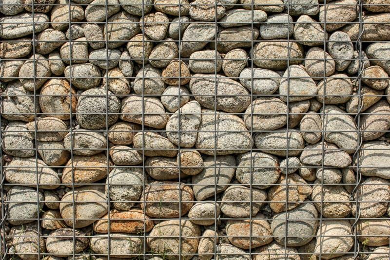 Muur van ronde die rotsen wordt gemaakt, met het netijzer dat van de staaldraad ston worden beveiligd royalty-vrije stock afbeeldingen