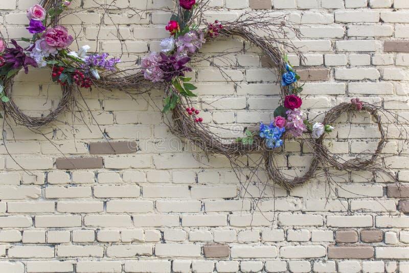 Muur van witte en bruine bakstenen met ronde ringen van droge takken van verschillende grootte en kleurrijke bloemen Ruwe Oppervl royalty-vrije stock afbeelding
