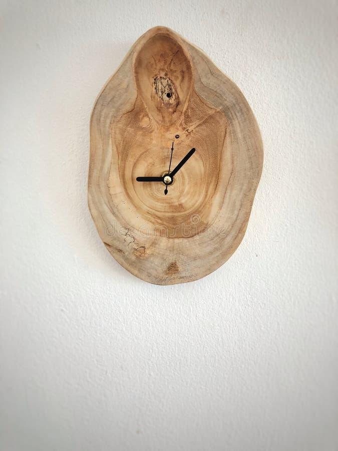 Muurklok door houten op de witte muur wordt gemaakt die stock afbeelding