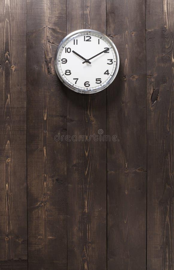 Muurklok op houten achtergrond stock fotografie