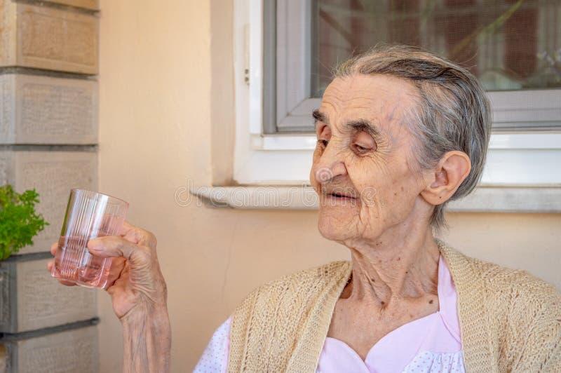 Muy vieja mujer mayor en el balcón que sostiene un vaso de agua en su mano foto de archivo libre de regalías
