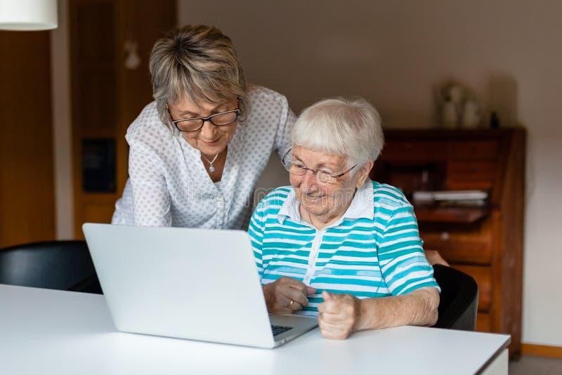 Muy vieja mujer mayor que aprende utilizar un ordenador fotos de archivo libres de regalías